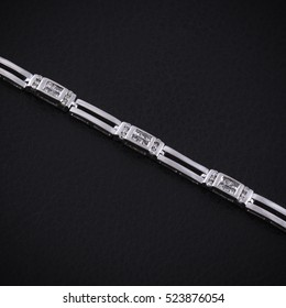 White gold bracelet with diamonds on texture of black leather