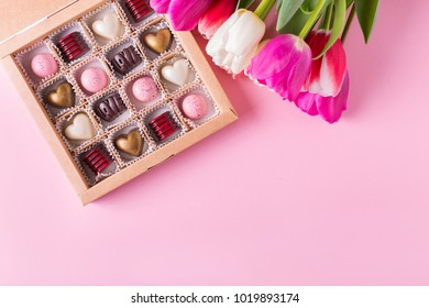 White and gold  chocolate candies in the shape of heart on a pink background. Assorted sweets in a box and tulips