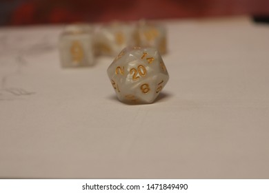 A white and gold D20 in the foreground on a white canvas.  It is showing the number everyone wants to see.
