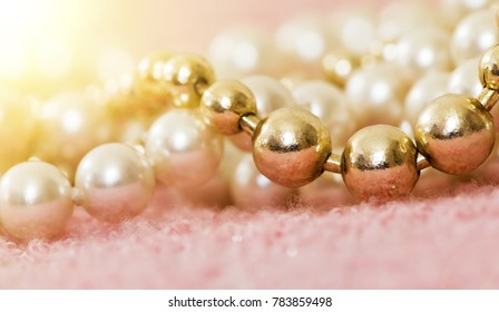 White and gold pearl necklace gift on pink background