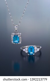 A white gold pendant and ring are set with blue topaz emerald cut gemstones and surrounded by accent diamonds.