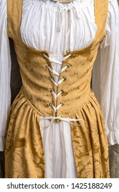 White and gold Renaissance period woman's dress with corset lace tie around the waist.