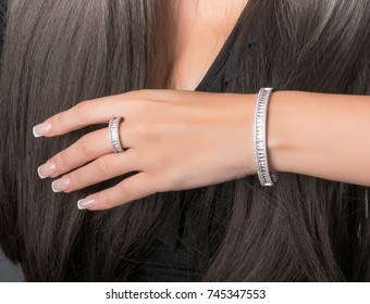 white gold ring and bracelet set on a hand with French manicure