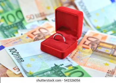 White gold ring in a red box with Euro banknotes in background