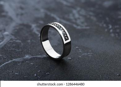 White gold wedding ring with black gemstones on black background. Fashion mens jewellery