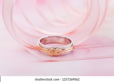 White gold wedding rings with pink gold knot on pink background with ribbon. Conceptual silver and gold wedding fashion jewelry for her