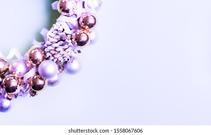 White and golden ornaments Christmas wreath on trendy lilac blue background. Modern minimal festive concept.