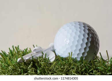 Closeup view of white golf ball and fixtures laid on artificial grass on white background