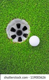 A white golf ball near the hole