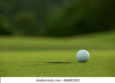 white golf ball near hole on fairway with the green background in the country side