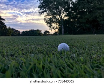 The white golf ball is on the grass in the field at the golf course in Thailand.