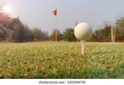 The white golf ball on the green green on the sun shines before the horizon./In Thailand /sea