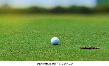 White Golf ball on green course near hole on blurred landscape of golf course in bright day time with copy space. Sport, Recreation, Relax in holiday concept