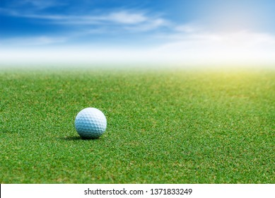 White Golf ball on the green grass on blurred blue sky with clouds background.
