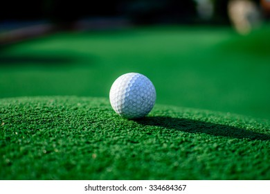 White golf ball on green grass in sunny day