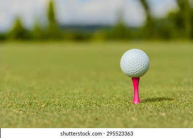 White golf ball on a pink tee