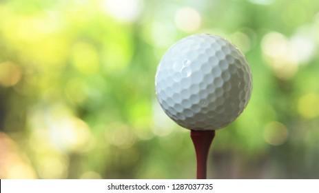 white golf ball on red tee green bokeh background