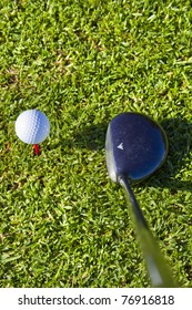 white golf ball on red tee in grass with driver close up ,ready to be hit, shot from above