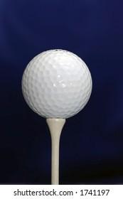 A White golf ball on a White tee against a dark blue background