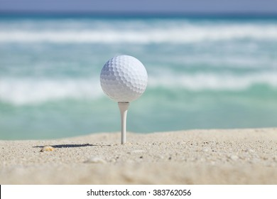 White golf ball on tee in sand of beach with soft focus ocean waves behind