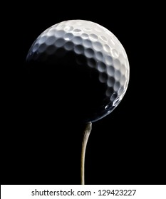 White Golf Ball on a Wooden Tee with dramatic lighting on black
