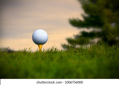 White Golf Ball on Yellow Tee with Grass in the Foreground and Pink Sky