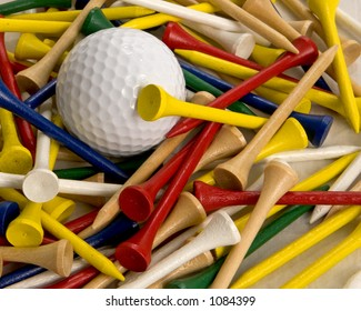 White golf ball surrounded by different color tees.