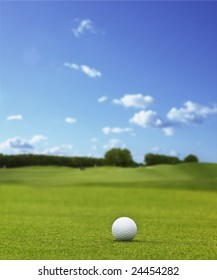 A white golfball laying at a golf course under blue sky