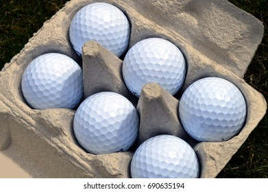White golfballs in a cardboard egg carton