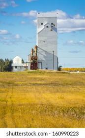 A white grain elevator in a small prairie town in Canada