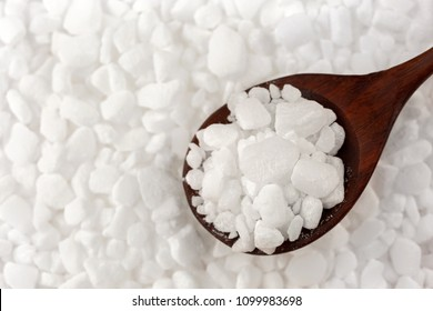 White granulated Dishwasher salt to soften water, Salt in wooden spoon, top view