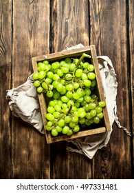 White grapes in an old box. On wooden background.