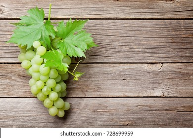 White grapes on wooden table. Top view with space for your text