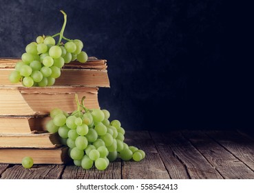 White grapes over old books on table in front of stone wall with copy space. Toned