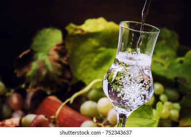 White grappa on wooden background, fresh grapes, selective focus