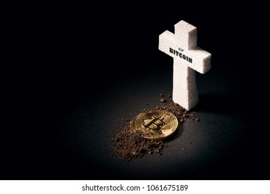 white grave cross and bitcoin sprinkled with earth. The concept of the fall of the cost of bitcoin and its death as the most expensive crypto currency