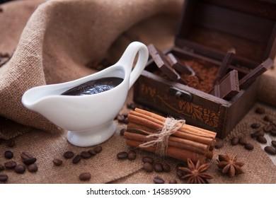 white gravy boat with cinnamon sticks and chocolate
