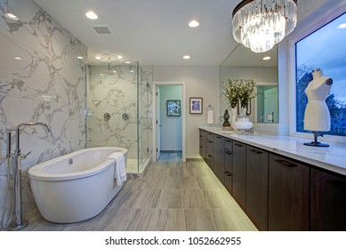 White and gray calcutta marble bathroom design with tiled floors, quartz counters, floating cabinets and freestanding tub.