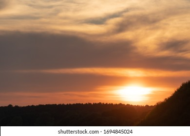 white and gray clouds are illuminated by the bright light of the setting sun. The sun is already on the horizon. Sunset or sunrise over the forest