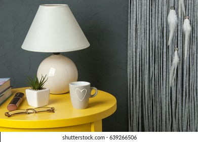 White gray dream catcher ,yellow bedside table , lamp, plant and mug in bedroom interior on dark gray textured background. Bedroom decor