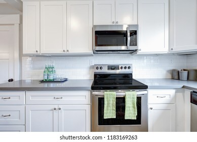 White and gray kitchen room with modern stainless steel appliances,  quartz countertops and subway tile backsplash.