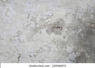 White and gray old surface. Exterior wall of a building made of stone and concrete, and painted with white paint. Interesting rustic texture of and old wall.