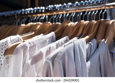 white and gray tone clothes hanging on a rack in a designer clothes store, selective focus, horizontal