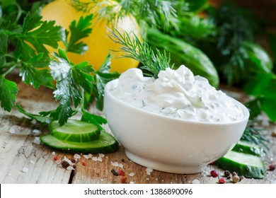 White greek sauce in white bowl with cucumber, lemon juice, herbs and spices on old wooden table, selective focus