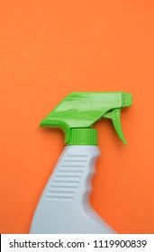 White and green cleaning spray bottle on an orange background