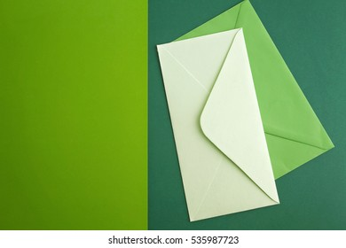 White and green envelope on colourful greenery background. Minimal concept