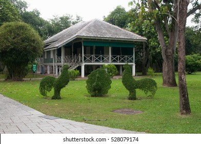 A white and green house with topiary birds in front