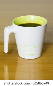 White and green mug on wooden table