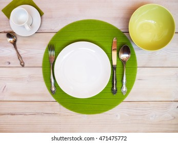 White and green plates and bowls on the table. View from above
