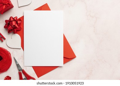 White Greeting Card and Red Envelope Mockup with copy space for text and romantic objects around like heart, bow, red scissors. Great for Valentine's Day and Romantic Presentations